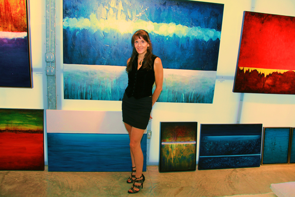 Leanne Venier in her Austin Gallery in front of her BLUE painting, Luminous Tranquility